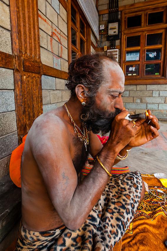 Saddhu (Holy man) smoking hash at a Hindu temple in Old Manali, Himachal Pradesh, India.