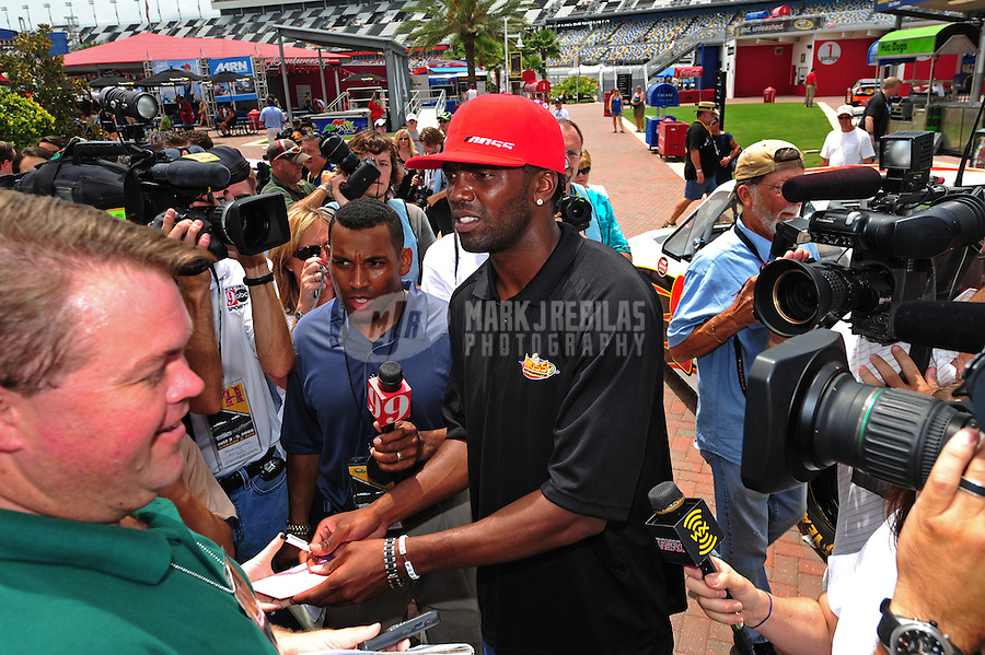 Jul. 3, 2008; Daytona Beach, FL, USA; New England Patriots wide receiver Randy Moss signs autographs after announcing his co-ownership of a NASCAR Craftsman Truck Series team prior to practice for the Coke Zero 400 at Daytona International Speedway. Mandatory Credit: Mark J. Rebilas-