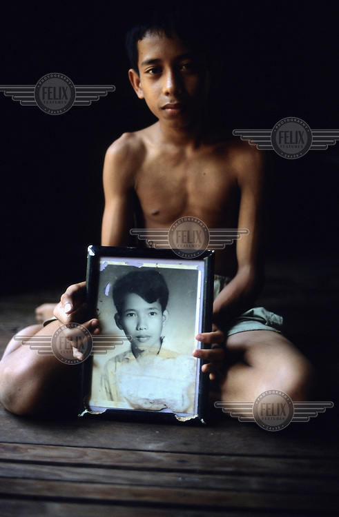 Hang Thai An, son of Comrade Duch, holds up a photograph of his father at the family home. Duch (real name Kaing Guek Eav) was chief executioner of the Khmer Rouge, responsible for the S-21 detention centre at Tuol Sleng, where over 16,000 people were killed between 1975 and 1979. Photographer Nic Dunlop unearthed Duch working with the American Refugee Committee in 1999. He is currently awaiting trial.