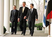 Washington, DC - December 15, 1999 -- United States President Bill Clinton escorts Shara and Barak to the opening statements prior to their trilateral meeting in the Oval Office on 15 December, 1999.  From Left to Right: Minister Farouk al-Shara, Foreign Minister of Syria; THE PRESIDENT; Prime Minister Ehud Barak, Prime Minister of Israel..Credit: Ron Sachs - Pool