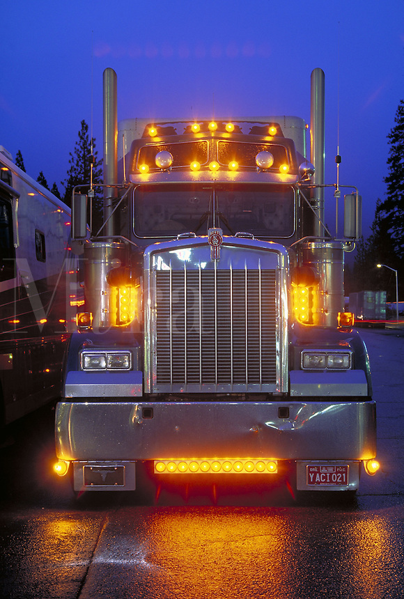 front view of semi truck with lights on and reflecting on wet road at dusk. trucking, transportation. CA USA.