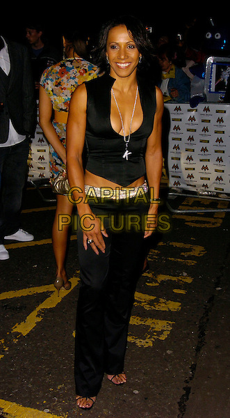 DAME KELLY HOLMES.MOBO Awards 2006, Royal Albert Hall, London, UK.September 20th, 2006.Ref: CAN.Mobos full length black trousers vest cleavage plunging.www.capitalpictures.com.sales@capitalpictures.com.©Can Nguyen/Capital Pictures.
