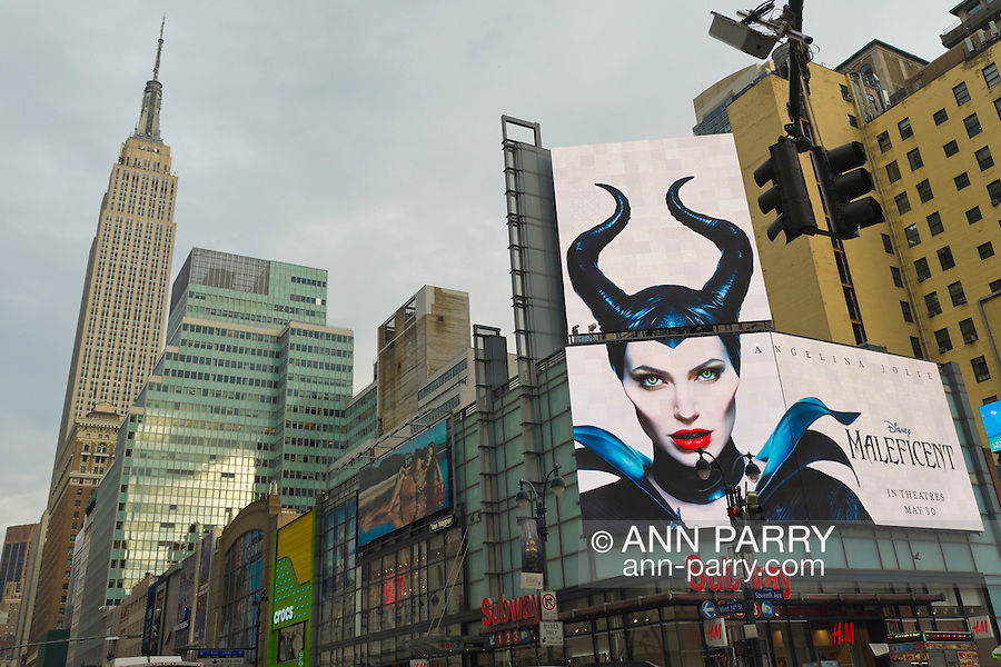 Manhattan, New York, U.S. - May 21, 2014 - A large overhead billboard on 7th Avenue advertises upcoming Disney movie Maleficent, starring actress Angelina Jolie, with Empire State Building at left in background, during a pleasant Spring day in Manhattan.