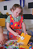 Nursery school girl helping to clean toys in large wash basin using scrubbing brush,