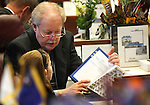 Nevada Sen. Mike Schneider, D-Las Vegas, shows his grand-niece Haley Hill, 10, a thick book of bills at his Senate desk at the Legislature in Carson City, Nev. on Monday, Feb. 7, 2011. Nevada lawmakers convened Monday for the 76th regular Legislative session. (AP Photo/Cathleen Allison)