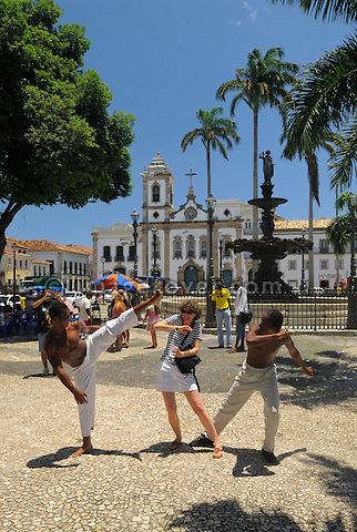 Brazil, Bahia, Salvador: Female tourist receiving a martial arts demonstration on the plaza Terreiro de Jesus with its church Igreja Sao Pedro dos Clerigos in Pelourinho, the beautifully restored historic center of Salvador de Bahia. --- Info: The district Pelourinho was built by the Portuguese in the 18th and 19th century as a residential and administrative center. Neglected for a greater part of the 20th century, Pelourinho received in 1985 the status as a UNESCO World Heritage Site. Restored it is today the crown jewel of Salvador. --- No signed releases available.