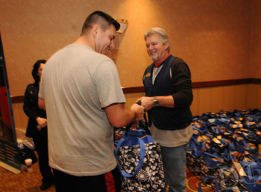 NWA Democrat-Gazette/FLIP PUTTHOFF<br /> Cody Henry (left) geats a Christmas meal bag Saturday Dec. 12, 2014 from Bob Blumenstein. Walmart associates and volunteers handed out the bags containing ingredients for a Christmas dinner.