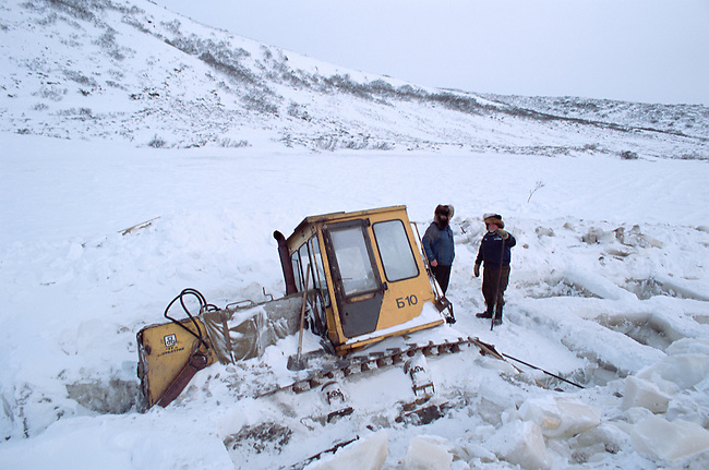 Workers trying to free a bulldozer that has fallen through lake ice on a winter road near Evensk. Magadan Region. Eastern Siberia, Russia