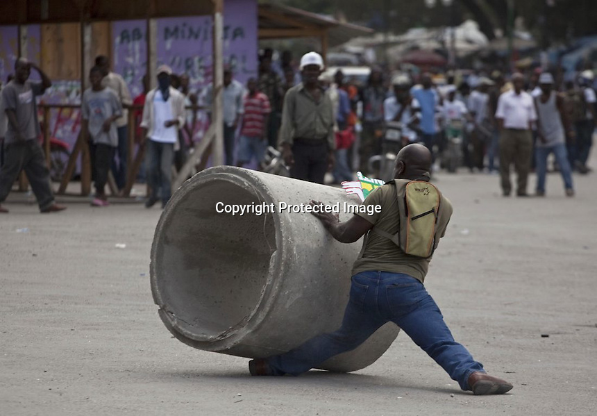 "A demonstrator tries to stop a concrete pipe from crushing his leg during a protest against Haiti's President Rene Preval in Port-au-Prince, Haiti, Monday Feb. 7, 2011. ""Protest Crush"" Photo by Ramon Espinosa/The Associated Press"