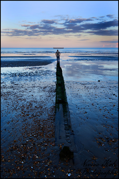 Man walking along a groyne on the beach