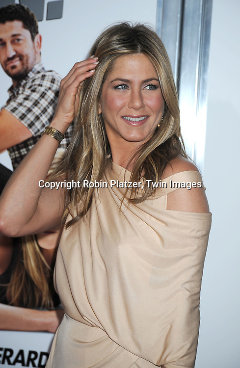 "actress Jennifer Aniston in Donna Karan beige dressattending the New York Premiere of ""The Bounty Hunter"" on March 16, 2010 at The Ziegfeld Theatre. The movie stars Gerard Butler and Jennifer Aniston."