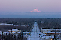 Alpenglow lights the summit of Mount Redoubt volcano as morning traffic moves down a street in Soldotna, Alaska. The 10,197-foot volcano is about 50 miles across Cook Inlet from the central Kenai Peninsula town.