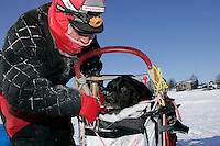 "Tuesday March 6, 2007   Ramy Brooks works on getting ""Burt"" out of his sled bag at the Nikolai checkpoint on Tuesday.  Burt injured himself about 1/3 of the way on the run from Rohn forcing Ramy to carry him in the basket."