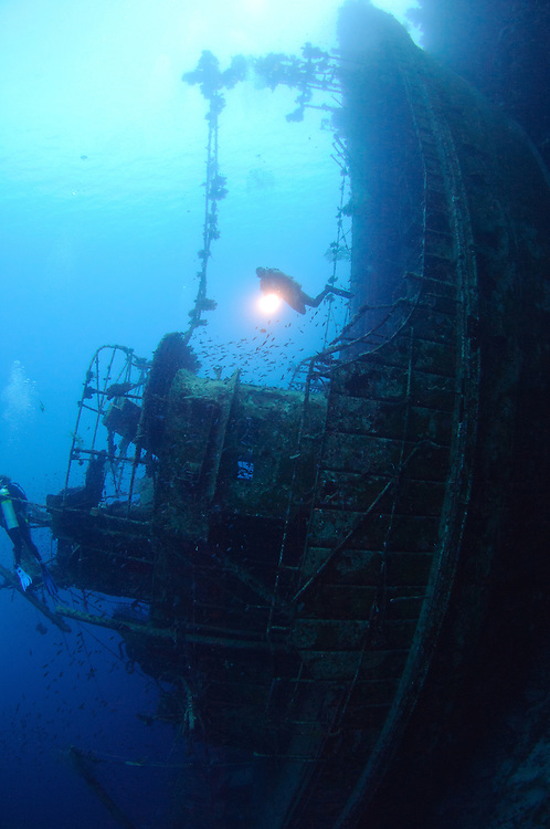 A diver explores the wreck of the Soltai 61 that lies vertically jammed against a reef, Solomon Islands