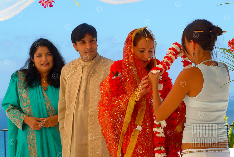 Tradditional Hindi wedding with groom about to receive carnation flowers from his bride
