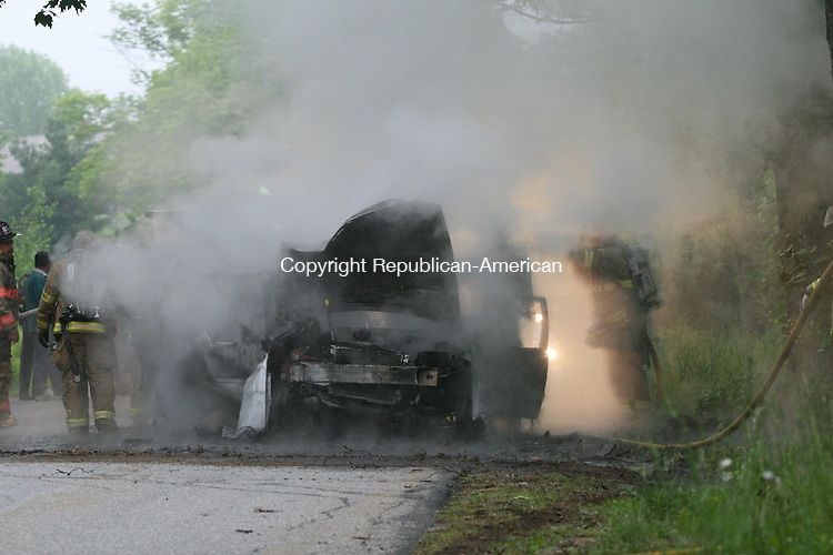 LITCHFIELD, CT - 27 May, 2009 - 052709MO04 - Firefighters douse the wreck of a Volvo XC 70 destroyed in a one car-crash in Litchfield Wednesday evening. The driver, who was apparently unhurt, was taken into police custody following field sobriety tests. A veterinarian was summoned from Farmington to provide emergency care for an injured puppy rescued from the vehicle. Jim Moore Republican-American.
