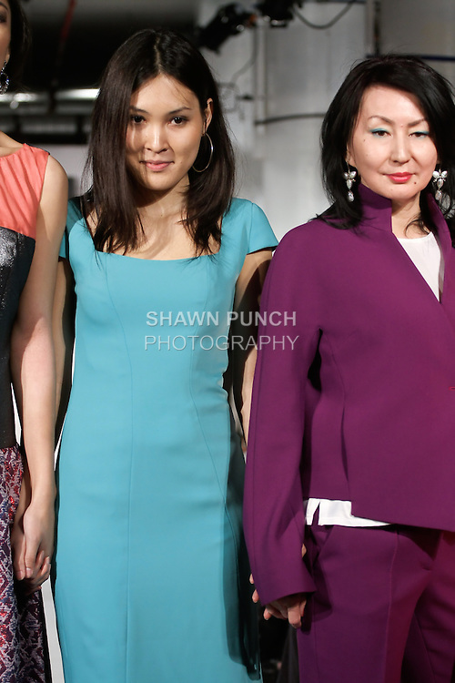 Fashion designer Nurjamal Nurpeisova poses on the runway with her daughter and models, at the close of her Nur-Shah Fall Winter The Princess of China collection fashion show, during BK Fashion Weekend Fall Winter 2012.