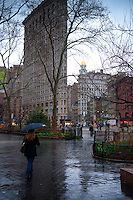 Lady walk under rain in Madison Square park to Flatiron building, Manhattan, NYC