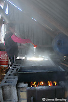 Young girl boiling sugar maple sap in a sugar shack