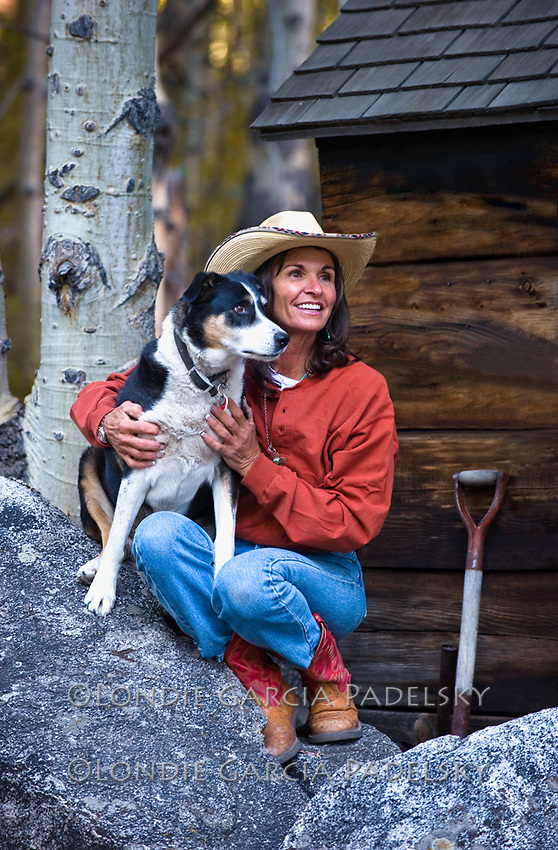 Cowgirl sitting with her dog. Eastern Sierra, California