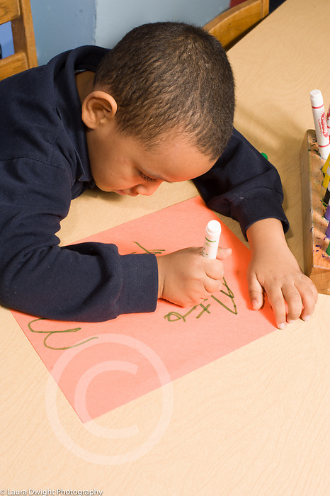 Educaton preschool 4-5 year olds art activtity boy drawing or writing letters with marker vertical using right hand