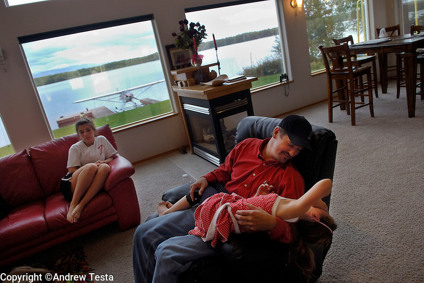 USA. Wasilla.  13th September 2007.Todd Palin. the Governor's husband, with their daughters Piper and Willow, at their home in Wasilla. .©Andrew Testa/Panos
