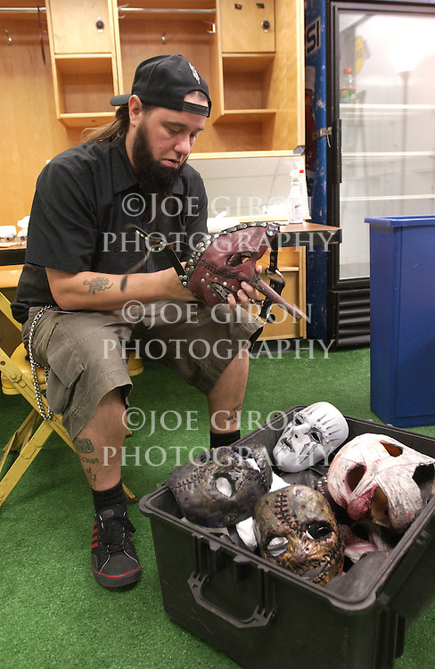 "Slipknot band assistant, ""Tongs"" wipes the  band's masks prior to their performance."