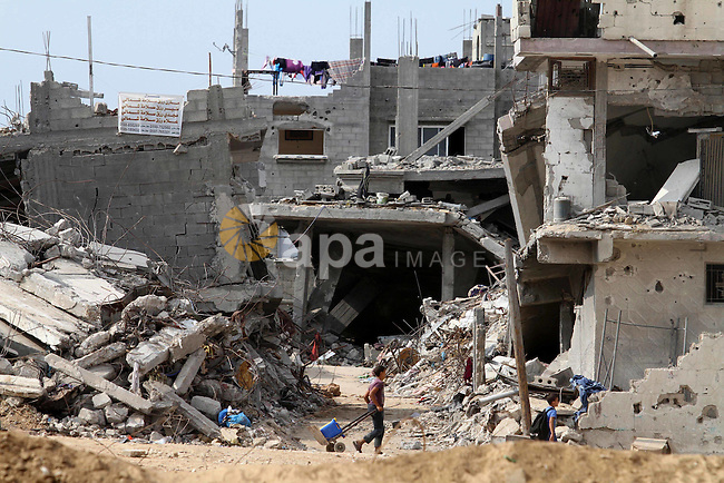 Palestinians children walk next to the destroyed homes houses and buildings that were destroyed during the devastating 50-day war between Israel and Hamas at Al-Shojae'ya neighborhood east of Gaza City on October 11, 2014. ahead of a donors conference in Cairo aimed at gathering efforts to the reconstruction of the Gaza Strip after the devastating 50-day war between Israel and the Hamas militants who run the coastal Palestinian enclave. The Palestinian government has unveiled a 76-page reconstruction plan for Gaza, calling for $4 billion to rebuild the war-battered territory, with the largest amount going to build housing for some 100,000 left homeless. Photo by Mohammed Asad