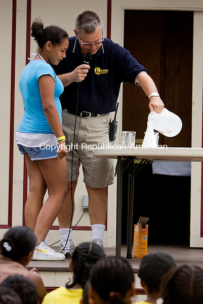 MIDDLEBURY, CT-  15 June 2010- 061610BF01- Ron Gustafson, director of public relations and educational programs at Quassy Amusement Park shows Nastalzha Ramos,13, an eighth-grade student at North End Middle School in Waterbury how to make a volcano using household items like baking soda during the Wacky Science presentation Wendesday at the park in Middlebury.  Bob Falcetti Republican-American
