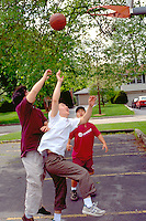 Korean American friends age 17 playing basketball.  WesternSprings Illinois USA