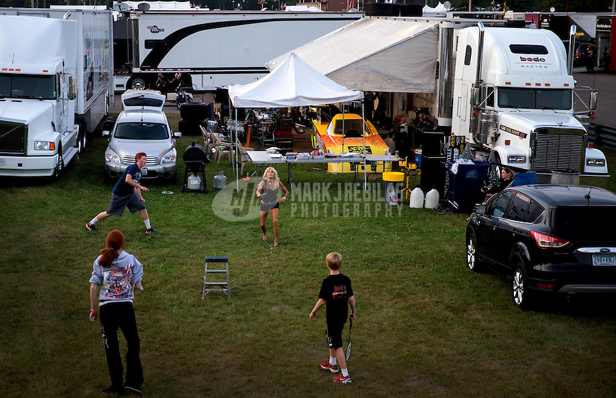 Aug. 17, 2013; Brainerd, MN, USA: Alice Bode , wife of NHRA funny car driver Bob Bode plays badminton with family and friends in the pit area following qualifying for the Lucas Oil Nationals at Brainerd International Raceway. Mandatory Credit: Mark J. Rebilas-
