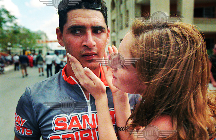 A Cuban cyclist's girlfriend welcomes him at the end of a stage in the Vuelta a Cuba (the Tour of Cuba cycling race).