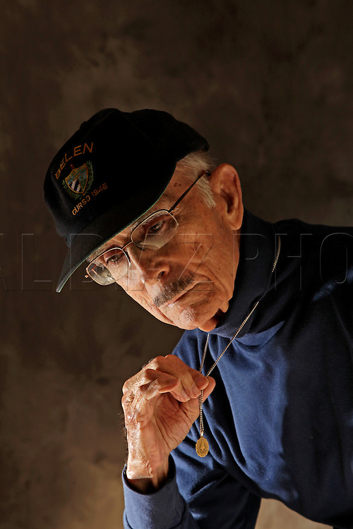 Jose Bertran holds a medallion he wore during the Bay of Pigs invasion in Cuba. He is a member of the Bay of Pigs Veterans Association, Brigade 2506.