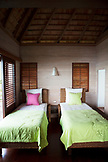FRENCH POLYNESIA, Moorea Island. Bungalows, Interiors and views of the Legends Resort Moorea. View of a bedroom of one of the bungalows.