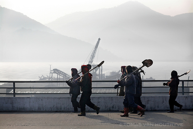 Korean women walk along the road carrying shovels on the outskirts of Pyongyang, North Korea (DPRK) on 29 February 2008.