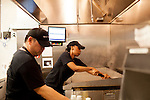 Gary Fontanilla and Kiana Coleman clean the grill and fryer at the end of a day at Grindhouse Killer Burgers in Terminal A at Hartsfield–Jackson Atlanta International Airport, in Atlanta, Georgia on August 28, 2013.