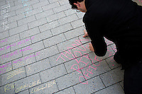 Damon Doucet, 2016 Course 6.3, writes a chalk message at a memorial as people gather along Vassar Street near the STATA Center on MIT's campus to form a human chain from the site of the killing of MIT Police officer Sean Collier to the headquarters of MIT Police on April 22, 2013. Collier is alleged to have been killed by the Tsarnaev brothers who are accused of detonating bombs at the 2013 Boston Marathon a week earlier.