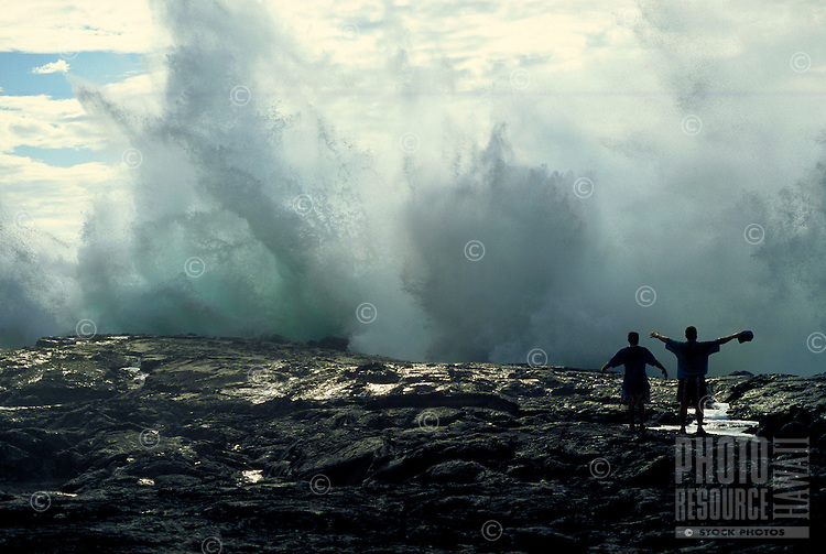 Teens enjoy the thrill of huge crashing waves on the black lava rocks on the Big Island of Hawaii.