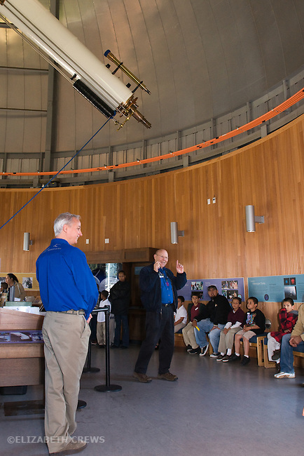Oakland CA Older man volunteer instructing visiting second grade students on school field trip about operation of major telescope at the Chabot Space and Science Center while docent looks on