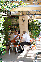 Street scene, men sitting at a cafe drinking coffee in the shade. Tirana capital. Albania, Balkan, Europe.