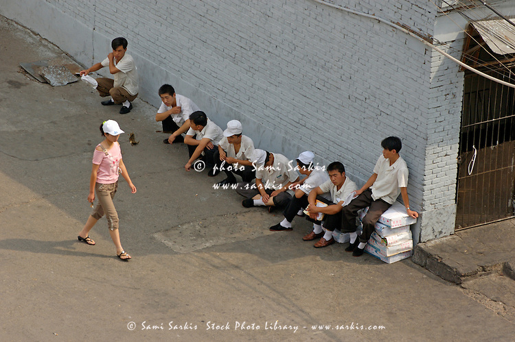 Restaurant workers having a break outside as a woman walks past, Datong, Shanxi, China.
