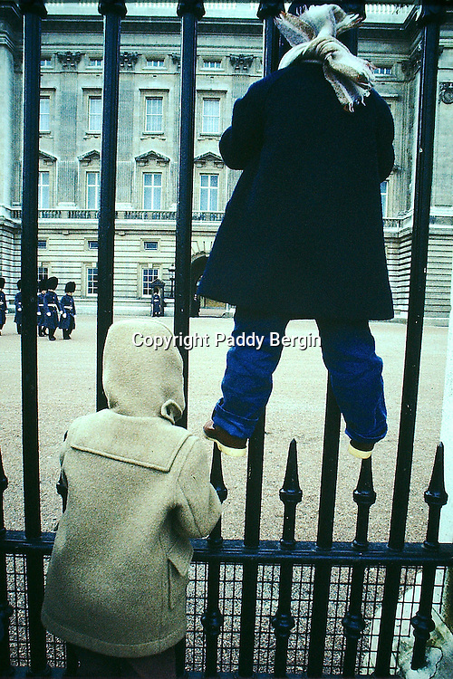 Young brothers viewing Buckingham Palace through the railings as the guard is changing.<br />