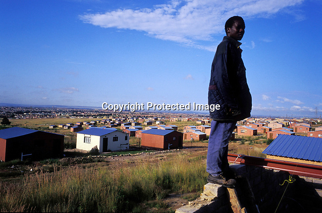 Township,RDP,housing,poverty,construction,black,building,middle-class,builder,.An unidentified man takes a break while working on the roof of a RDP (rapid development program) government sponsored house, also known as Mandela houses, on February 19, 2004 in Soweto outside Johannesburg, South Africa. The government promised to build one million houses during the election in 1994 and about 1,7 million houses have been built. Still the housing backlog are estimated to about 6-7 million units, making it still a dream for many poor people in South Africa to own a house. .©Per-Anders Pettersson/iAfrika Photos....