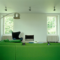 A black leather Egg chair by Arne Jacobsen beside a small modern fireplace and a vibrant green L-shaped sofa by Ligne Roset in the family room