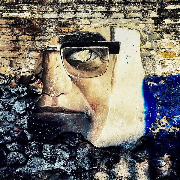 A broken mural depicting Óscar Romero, a former archbishop of San Salvador assassinated in 1980, is seen on the wall in the center of San Salvador, El Salvador, 9 April 2018.