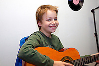 Happy boy age 10 taking a guitar music lesson. St Paul Minnesota USA