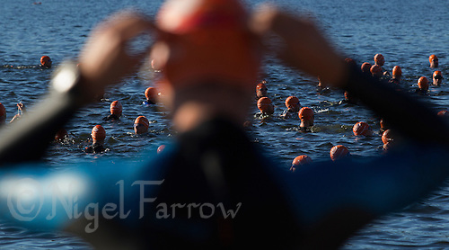 25 AUG 2013 - STOCKHOLM, SWE - A competitor adjusts his goggles before entering the water for his wave start of the Stockholm Triathlon in Stockholm, Sweden (PHOTO COPYRIGHT © 2013 NIGEL FARROW, ALL RIGHTS RESERVED)