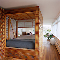 The sleeping area is enclosed in a box of slatted iroko and has a drop down window which provides a desk space