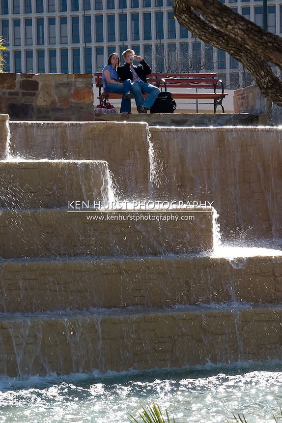 A young couple sit on a bench overlooking waterfalls at Hemisfair Park in San Antonio, Texas, USA.