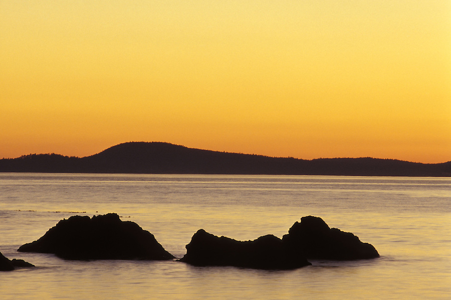 Sun setting Urchin Rocks and Vancouver Island, Deception Pass State Park, Fidalgo Island, Washington